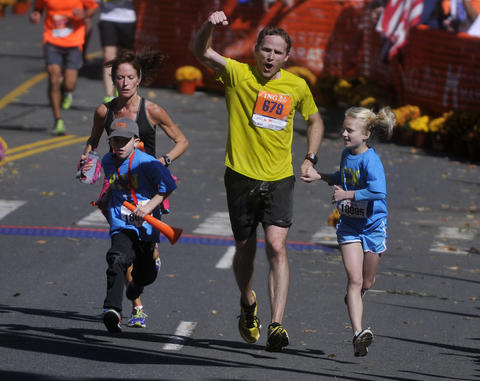Hartford - 10/12/13 - Tom Lowery, is joined by his son, Henry Lowery, 7, and his daughter, Sophia Lowery, 9, as he nears completion of the 20th running of the Hartford Marathon. The Lowery family is from Belmont, MA. Photo by BRAD HORRIGAN | bhorrigan@courant.com