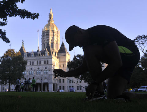Hartford - 10/12/13 - A runner laces up prior to the the 20th running of the Hartford Marathon. Photo by BRAD HORRIGAN | bhorrigan@courant.com