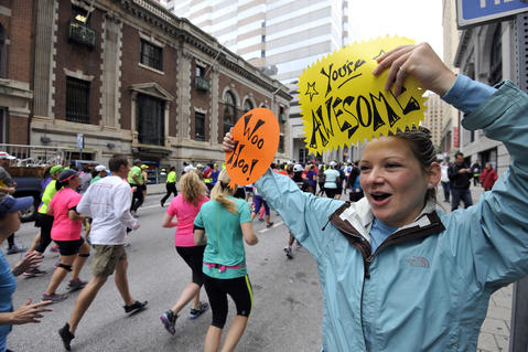 Vanessa Brown, Bethlehem, Pa., holds up two signs as runners in the half marathon of the Baltimore Running Festival pass by on Calvert Street. She came to support three friends running in the half marathon.