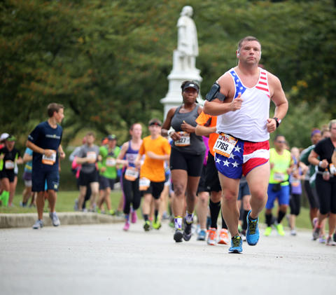 Runners at the Baltimore Marathon complete miles three and four at Druid Hill Park.