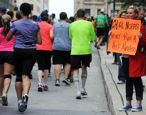 "Kimberly Morren of Laurel holds a sign that reads ""Chuck Norris Never Ran A Half Marathon"" as one of several groups of half marathoners run by on Calvert Street."