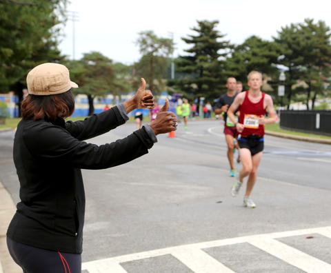 Runners at the Baltimore Marathon complete miles around Lake Montebello as S. Rivers from Michigan cheers them on.