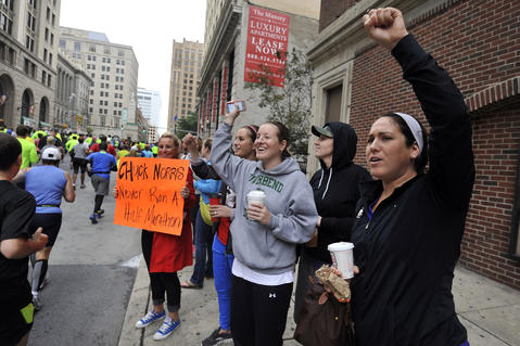Left to right, holding sign, Kimberly Morren, Laurel, Monique Mounce, Laurel, Kate Whalen, Baltimore, Megan Kuyper, Alexandria, Va., and Orly Rosenberg, Baltimore, cheer one of several groups of half marathoners as they begin their Baltimore Running Festival race on Calvert Street. They are there to support two of their friends running in the half marathon.