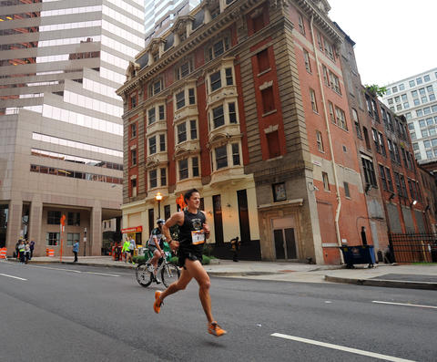 The eventual men's winner of the 2013 Baltimore Marathon runs along Light Street at about the nine mile mark of the race during the13th Annual Baltimore Running Festival.