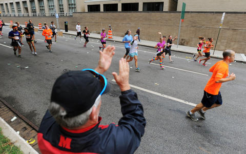 Bystander on St. Paul Street cheers on runners in the 2013 Baltimore Marathon during the13th Annual Baltimore Running Festival.