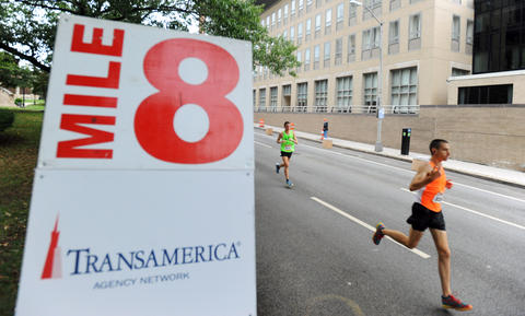 The 2013 Baltimore Marathon runners run by the 8 mile marker on St. Paul Street during the 13th Annual Baltimore Running Festival.