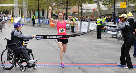The 2013 Baltimore Marathon women's winner Elizabeth Perry, center, of Pittsburgh, Pa., crosses the finish tape held by Boston Marathon bombing survivor Erika Brannock, left, and Md. Sen. Catherine Pugh during the 13th Annual Baltimore Running Festival. _KKL7081  sp-baltimore-marathon-p8-md-rewind-runningfest lam