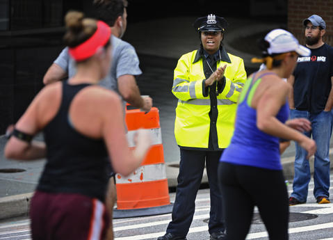 Baltimore City police officer Sharon Mason, center, cheers on runners of the 2013 Baltimore Marathon running pass her post on Light Street.