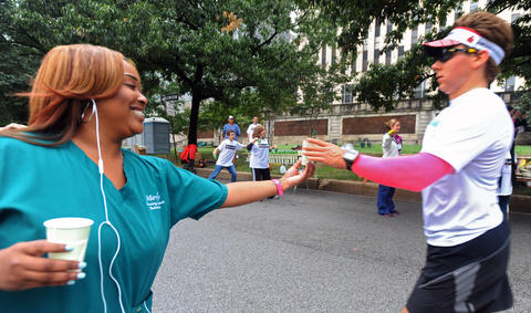 Akila Taylor, a nurse support tech at Mercy Hospital, volunteered to hand out water to runners at a water station in front of the hospital eight miles into the 2013 Baltimore Marathon.