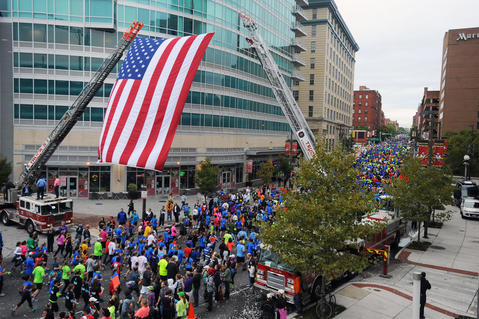 Runners in the 13th Annual Baltimore Running Festival 5K race run under a giant United States flag on Paca Street after the start of the race.