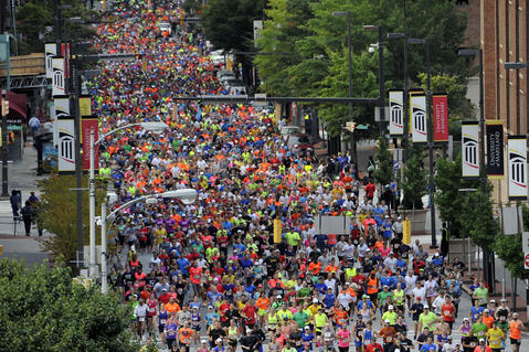 Runners begin the Baltimore Running Festival marathon on Paca Street.