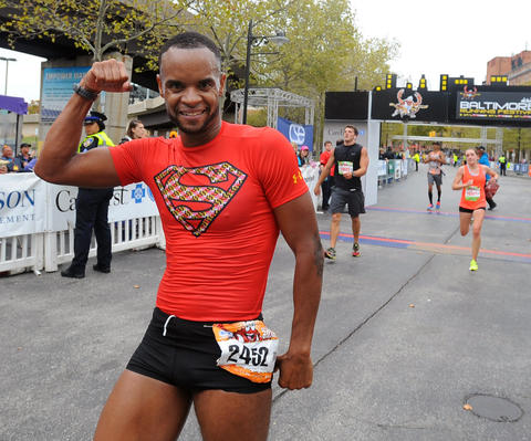 Remus Medley, of Baltimore, flexes his bicep as Superman after he finished the 2013 Baltimore Marathon.