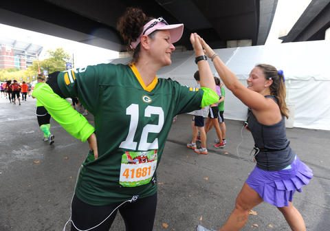 Sue Yerkes, of Wilson, N.C., dressed in a Green Bay Packers Aaron Rodgers jersey, gets high fives from fellow runner at the 13th Annual Baltimore Running Festival.