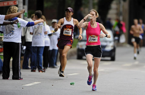The eventual women's winner Elizabeth Perry (#2789) gets a drink at a water station on St. Paul Street eight miles into the 2013 Baltimore Marathon.