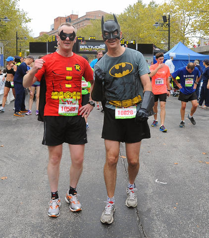 "Ged Moretta, left, of Liverpool, England, and Pete Stine, of Baltimore, who were dressed as the ""dynamic duo"" Robin and Batman, posed at the finish of the 13th Annual Baltimore Running Festival. They ran in the half marathon."