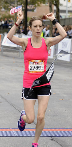 The 2013 Baltimore Marathon women's winner Elizabeth Perry, of Pittsburgh, Pa., crosses the finish line during the 13th Annual Baltimore Running Festival.