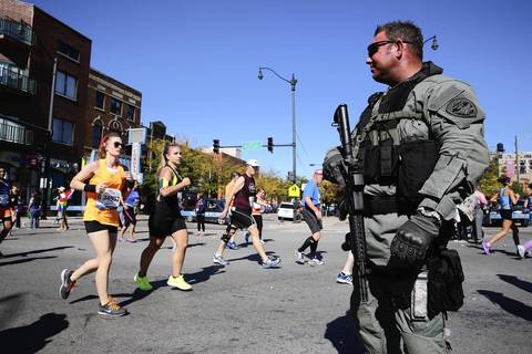A member of the Cook County Sheriff's Police Hostage, Barricade and Terrorist Team watches over the marathon on 18th Street in Chicago's Pilsen neighborhood.
