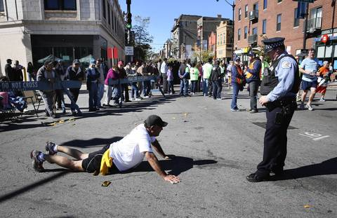 Runner Jim Meinecke uses a police officer's baton to try and roll out a cramp in his quadricep as he stops on 18th Street in Pilsen.