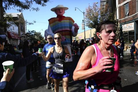 Large puppets dwarf the runners who race down 18th Street in the Pilsen neighborhood of Chicago.
