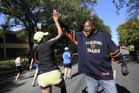 Charles Thomas, of Chicago, greets runners at 35th and South Michigan Avenue with high fives as they get near the end of the marathon route.