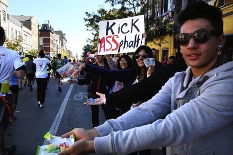 Pilsen residents hand out candy and cheer the runners along the Bank of America Chicago Marathon race route in Pilsen.