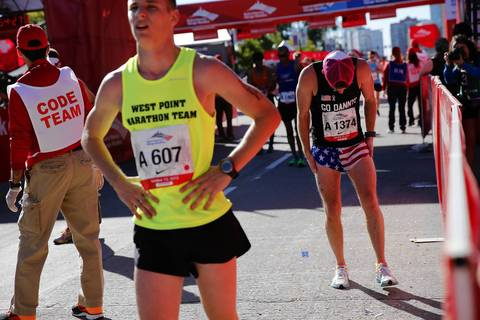 Danny Corken, of Chicago, right, bends over after completing the 2013 Bank of America Chicago Marathon.
