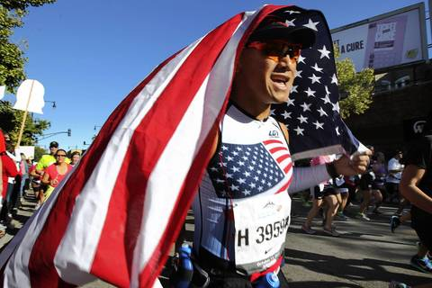 A Chicago Marathon runner dressed in American clad runs past crowds of spectators lined up on Broadway Avenue in the Boystown neighborhood of Chicago.