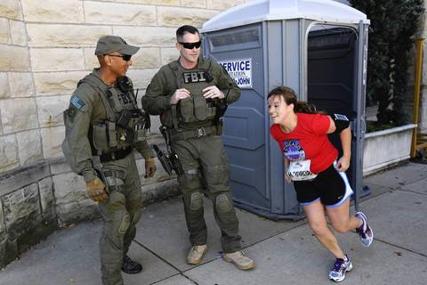 A runner races back to the streets after a bathroom break passing by two FBI agents in full gear.