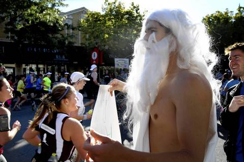 Tom Fell, of Chicago, dressed as an ancient Greek, cheers on Chicago Marathon runners as he and thousands of other spectators line Broadway Avenue in the Boystown neighborhood of Chicago.