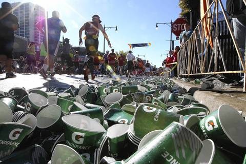 Empty cups line Broadway Avenue in the Boystown neighborhood of Chicago as Chicago Marathon runners head up the street.