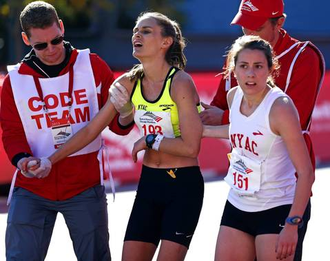 Caitlin Phillips, from New York is helped by race officials and Ellen Dougherty, also from New York, at the finish line of the 2013 Bank of America Chicago Marathon.