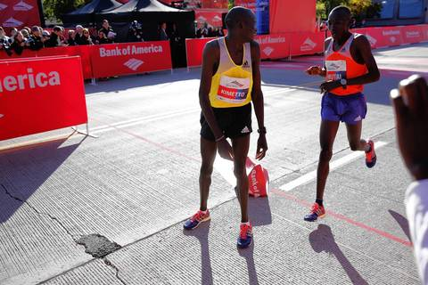 Bank of America Chicago Marathon winner Dennis Kimetto, left, watches second place finisher Emannuel Mutai cross the finish line. Both men are from Kenya.