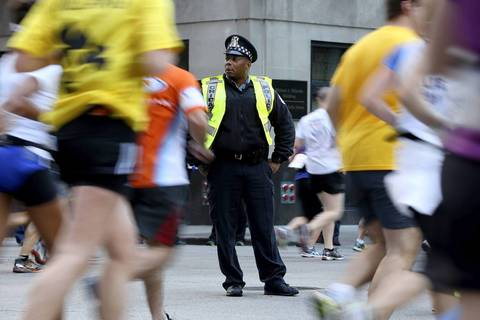 A Chicago Police officer on LaSalle Street keeps a close watch on the runners and crowd.