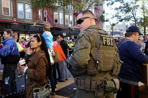 An FBI agent looks carefully at the crowd as he walks down Broadway Avenue in the Boys Town neighborhood of Chicago during the Chicago Marathon.