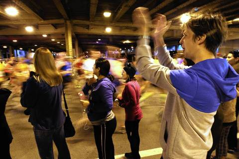 Runners pass under Grand Avenue in downtown Chicago.