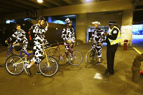 A Chicago Police officer talks with marathon spectators dressed in cow outfits under Michigan Avenue at Grand Avenue.