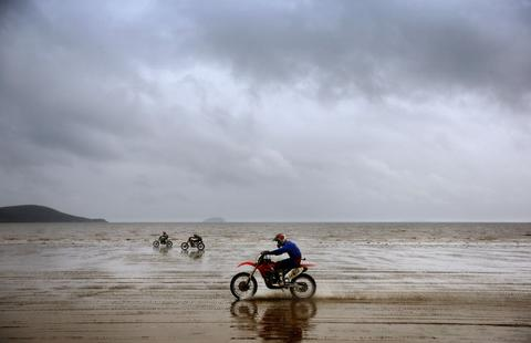 Riders race down the beach during the main solo race during the 2013 RHL Weston beach race in Weston-Super-Mare, southwest England, on October 13, 2013.   Beach racing is an offshoot of enduro and motocross racing. Riders on solo motorcycles and quad bikes compete on a course marked out on a beach, with man-made jumps and sand dunes being constructed to make the course tougher. Riders race along the beach and across a series of sand dunes in a three-hour endurance race.