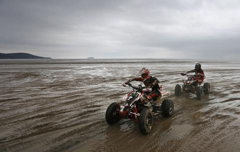 Riders take a corner on their quad bikes during the 2013 RHL Weston beach race in Weston-Super-Mare, southwest England, on October 13, 2013.  Beach racing is an offshoot of enduro and motocross racing. Riders on solo motorcycles and quad bikes compete on a course marked out on a beach, with man-made jumps and sand dunes being constructed to make the course tougher. Riders race along the beach and across a series of sand dunes in a three-hour endurance race.