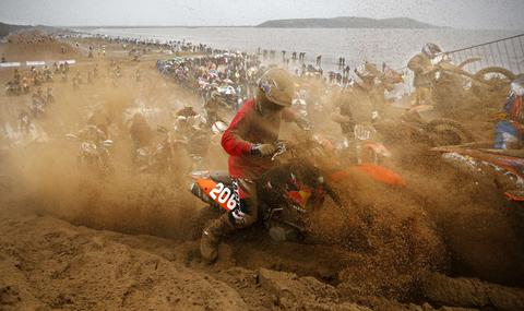 Steve Price gets covered in sand as he rides his KTM up dune 18 during the main race of the 2013 RHL Weston beach race in Weston-Super-Mare, southwest England, on October 13, 2013.  Beach racing is an offshoot of enduro and motocross racing. Riders on solo motorcycles and quad bikes compete on a course marked out on a beach, with man-made jumps and sand dunes being constructed to make the course tougher. Riders race along the beach and across a series of sand dunes in a three-hour endurance race.