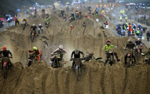 Riders reach the crest of a dune during the opening lap of the main race of the 2013 RHL Weston beach race in Weston-Super-Mare, southwest England, on October 13, 2013.  Beach racing is an offshoot of enduro and motocross racing. Riders on solo motorcycles and quad bikes compete on a course marked out on a beach, with man-made jumps and sand dunes being constructed to make the course tougher. Riders race along the beach and across a series of sand dunes in a three-hour endurance race.