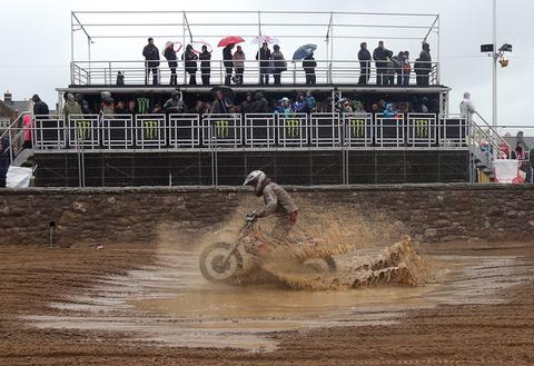 SOMERSET, UNITED KINGDOM - OCTOBER 13:  A rider splashes through a puddle of standing water as he competes during the main solo race of the 2013 RHL Weston annual beach race in Weston-Super-Mare on October 13, 2013 in Somerset, United Kingdom.  The three-hour endurance race, one of the largest of its kind in the UK, saw hundreds of riders competing on a course marked out on the beach, with man-made jumps and sand dunes being constructed to make the course tougher.