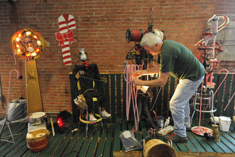 Artist Steve Gerberich adjusts part of the exhibit during installation.