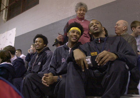 Carmelo Anthony (center sitting) leans over to talk to Chadd Moore. Justin Gray (left), Anthony, and Moore were members of the Oak Hill Academy boys basketball team in 2002.