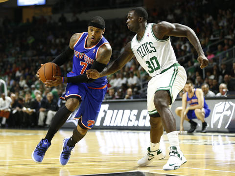 Carmelo Anthony drives to the basket against Boston Celtics forward Brandon Bass during a preseason game in Providence, R.I.