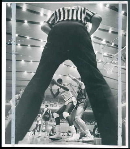 Referee Joe Gushue's split legs frame the action at the Civic Center as the Baltimore Bullets' Walt Bellamy is guarded by Gene Conley of the New York Knicks.