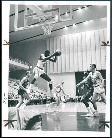 Bullets center Walt Bellamy goes high in the air to capture rebound during game at the Civic Center against the New York Knicks.