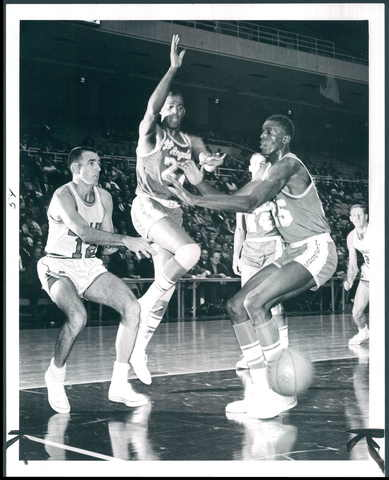 The Bullets' Gene Shue (left) makes a pass past the Lakers' Elgin Baylor and Leroy Ellis.
