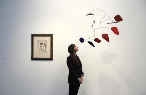 "A worker poses with ""Femme devant le soleil"" by Joan Miro (L) and ""Black and Blue"" by Alexander Calder during a private viewing of the Frieze Masters 2013 art fair in London October 15, 2013. Frieze Masters, showing works for sale from 130 galleries from around the world, opens Thursday and runs until October 20."