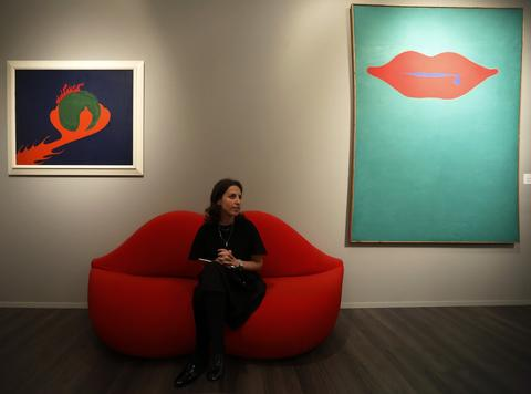 """Gallery worker Kimberley Williams poses with work by artist Jerzy 'Jurry' Zielinski """"Kito Ugasi (Quench the flame)"""" (L) and """"Czhanie pocalunku (Lurking kiss)"""" during a private viewing of the Frieze Masters 2013 art fair in London October 15, 2013. Frieze Masters, showing works for sale from 130 galleries from around the world, opens Thursday and runs until October 20."""