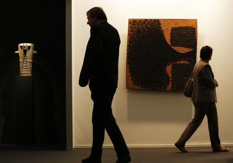 "Visitors pass an early 4th century BC Golan altar (L) and a 20th century work by Victor Pasmore ""Development No1"" during a private viewing of the Frieze Masters 2013 art fair in London October 15, 2013. Frieze Masters, showing works for sale from 130 galleries from around the world, opens Thursday and runs until October 20."